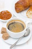 Breakfast with black coffee, croissants and orange jam — Stock Photo