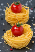 Italian egg pasta nest with cherry tomatoes, close-up — Stockfoto