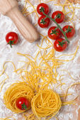 Italian pasta nest egg, cherry tomatoes and rolling pin — Stock Photo