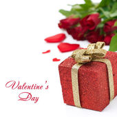 Red gift box and roses in the background, isolated — Stock Photo