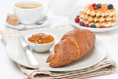 Sweet breakfast with croissant, jam, waffles, berries and coffee — Stock Photo