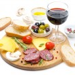 Salami, cheese, bread, olives, tomatoes and glass of red wine  — Stock Photo