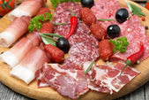 Assorted meats and sausages, olives and spices, close-up — Stock Photo