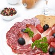 Assorted meat delicacies on a plate and a glass of wine — Zdjęcie stockowe