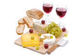 Cheese platter, grapes, bread and two glasses of red wine — Stok fotoğraf