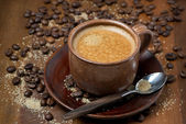 Cup of espresso, sugar and coffee beans on wooden table — Stock Photo