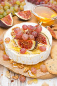 Camembert with grapes, figs, honey, crackers and walnuts — Stock Photo