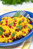 Couscous with curry, dried cranberries and herbs on the plate — Stock Photo