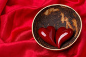 Two hearts in a bowl of coconut on red satin background — Foto Stock