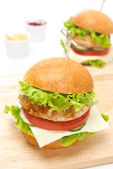 Chicken burger with vegetables, cheese on a wooden board — Stock Photo