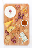 Assorted soft cheeses, grapes, nuts and honey on wooden board — Stock Photo
