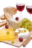 Kaasschotel, druiven, brood en twee glazen rode wijn — Stockfoto