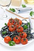 Black pasta with baked tomatoes and parsley, vertical — Stock Photo