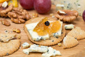 Crackers with blue cheese and apple jam, nuts and grapes — Stock Photo