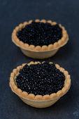 Tartlets with black caviar on a dark background — ストック写真