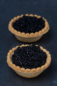 Tartlets with black caviar on a dark background — Stock fotografie