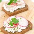 Grain bread with soft cheese, radish and herbs on a wooden board — Stock Photo #39904665