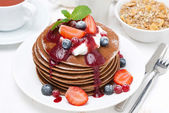 Pancakes with cream, fruit sauce and fresh berries for breakfast — Stock Photo