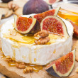 Camembert cheese with honey, figs and crackers on a wooden board — Stock Photo #40992767