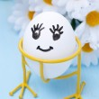 Funny smiling egg on stand and flowers for Easter, close-up — Stock Photo #40992769
