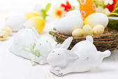 Easter rabbits and basket with eggs — Stock Photo