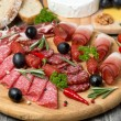 Assorted meats and sausages, olives and spices on a wooden board — Stock Photo