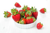 Fresh ripe strawberries in a bowl on a white table — Stock Photo