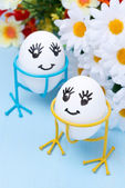 Two funny smiling eggs on stands and flowers for Easter — Stock Photo