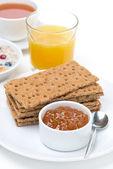 Fresh breakfast - crisp bread with jam, orange juice, tea — Stock Photo