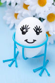Funny smiling egg on stand and flowers, close-up — Stock Photo