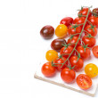 Colorful cherry tomatoes on a wooden board, isolated — Stock Photo #41925341
