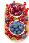 Fresh cherries, blueberries and red currants in a wooden bowl — Stock Photo