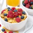 Cornflakes with berries in a bowl, milk and orange juice — Stock Photo #42473733