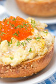 Scramble eggs with red caviar on a wheat bun, close-up — Stock Photo