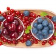 Cherries, blueberries and red currants in a wooden bowl isolated — Stock Photo #42856957