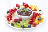 Frutas sortidas com molho de chocolate num prato — Fotografia Stock