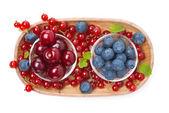Körsbär, blåbär och röda vinbär i en träskål som isolerade — Stockfoto
