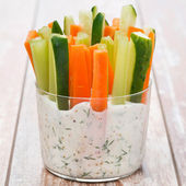 Fresh vegetables in a yoghurt sauce in a glass on wooden table — Stock Photo