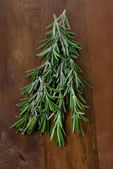 Fresh rosemary on a wooden table — Stock Photo
