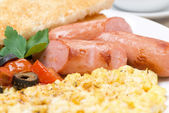 Grilled sausages, scramble eggs and tomatoes — Stock Photo