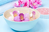 Flowers in a blue bowl, towels and sea salt for the spa — Stock Photo