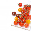 Colorful cherry tomatoes on a white wooden board, top view — Stock Photo #43214969