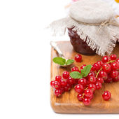 Fresh red currant and berry jam on a wooden board, isolated — Stock Photo