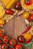 Pasta, spices and cherry tomatoes on a wooden board — Stock Photo