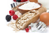 Oatmeal, flour, milk, eggs and berries - ingredients for baking — Stock Photo
