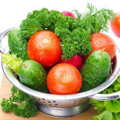 Fresh vegetables and herbs in a metal colander, close-up — Stock Photo
