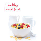 Cornflakes with fresh berries in a bowl and milk, isolated — Stock Photo