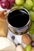 Glass of red wine close-up, cheese and grapes, top view — Stock Photo