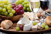 Camembert, fresh baguette, grapes and wine on a wooden tray — Stock Photo