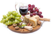 Two glasses of wine, grapes and cheese on a wooden board — Stock Photo
